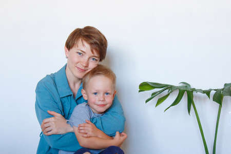 mother's day. mother's love. A happy mom with son in blue cloth embrace. Isolated on a white background. copy space. palm tree in pot. Game with child