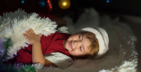a child in a Santa hat is sleeping New year. the concept of celebrating, enjoying Christmas at midnight. holiday costume