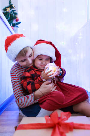children in Christmas costumes with a Christmas tree toy. concept of new year, masquerade, holidays, decorations