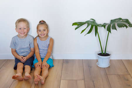 a boy and a girl are sitting on the floor. Children together at home