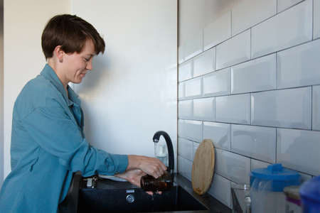 a woman washes dishes. washing the cup in the black sink Banco de Imagens