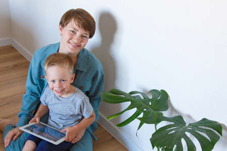 modern technologies in everyday life a woman and child look at a tablet on the floor. Hobbies and recreation with gadgets. Family vacation, spend time mom and son together at home. mother's love