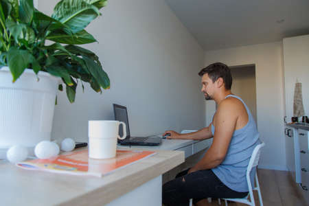 the concept of employment, interviews, advertising of digital technologies-a man in home clothes works at a laptop at home Banco de Imagens