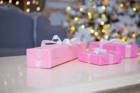 two beautiful pink gifts with bows on a wooden background with bokeh lights in the background. Christmas theme, holiday card Banco de Imagens
