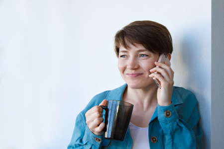 the concept of employment, interviews, advertising digital technology - woman drinking coffee and talking on the phone. Smiling woman with cup makes a call. Morning of girl