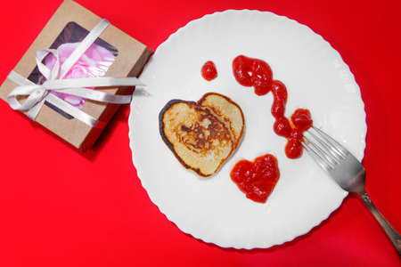 pancakes and ketchup in the shape of a heart on February 14. food for Valentine's day on a red background.