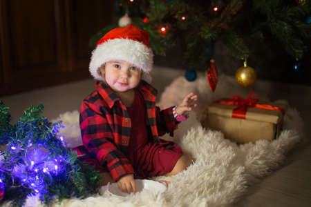 a child in red clothes is sitting waiting for the new year. the concept of celebrating Christmas at midnight. holiday costume