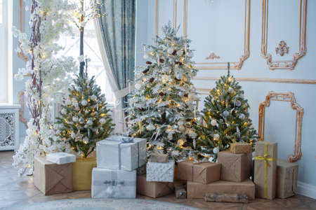 Festive interior: christmas tree and sofa with pillows, gifts. The concept of Christmas and the New year.