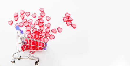 Valentine's day, endless love or special occasion concept: Top view of red hearts spilled out of a shopping cart. isolated on white background. copy space. 版權商用圖片