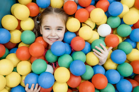a child in the children's playroom. The girl is having fun among the colorful balls. Dry pool party
