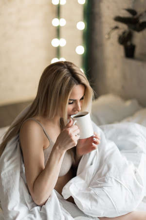 morning girls: the blonde with cup of tea, coffee. breakfast in bed. I just woke up. Standard-Bild