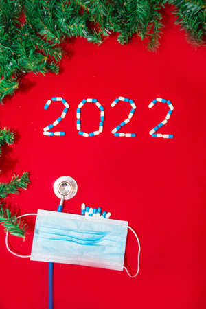 ncov-19 and the New year. Holiday in self-isolation, hospital. Christmas decorations and medical devices syringe and santa hat. Copy space on a red background