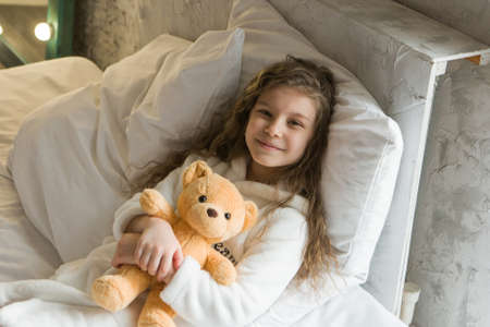 A beautiful girl with Teddy bear, a child with toy. The concept of childhood, morning pastime