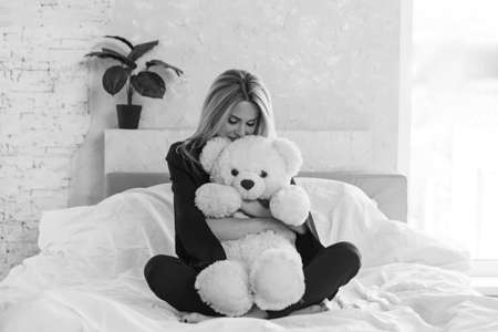 A beautiful girl with Teddy bear, a woman with toy. The concept of childhood, morning pastime