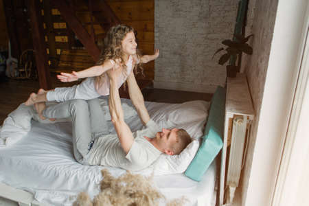 morning family: the children with dad playing in bed. waking up from a dream. I just woke up. love Standard-Bild