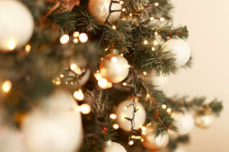 holidays, new year, decor and celebration concept - close up of christmas tree decorated with balls and toys
