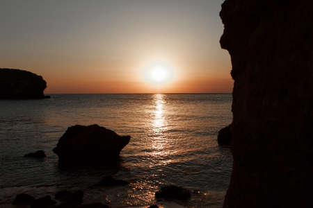 waves wash the rocky shore of the sea. Sunset. Reflection in the water of the bridge and rays