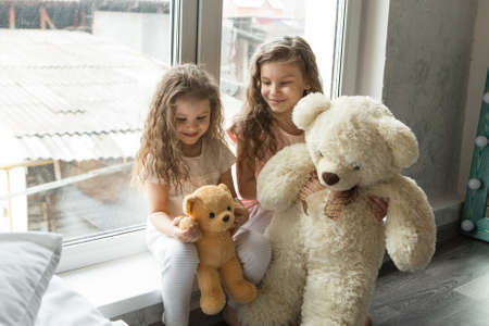 A beautiful girls with Teddy bear, a child with toy. The concept of childhood, morning pastime Standard-Bild
