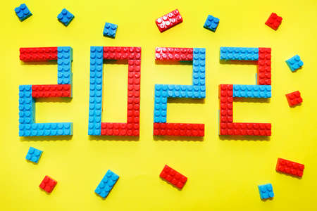 New year, 2022. Lettering from a childrens constructor on a yellow background. Toys in isolation. copy space. The concept of a hobby and learning Standard-Bild