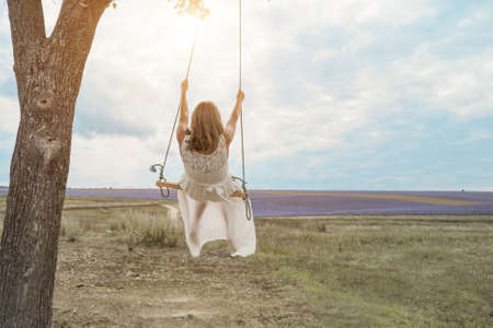 girl on a swing wrapped in green foliage. They are dressed in white robes. The sun shines on them Standard-Bild