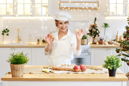 a cheerful chef prepares a Christmas cake. Lady cook in a cute apron breaking an egg into flour to make cake. The process of cooking. Step by step. Unsurpassed pre-holiday atmosphere and home comfort