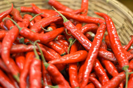 Fresh red chili peppers in wooden basket
