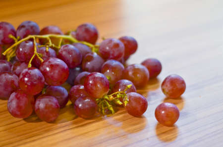 Fresh red grapes on wooden table