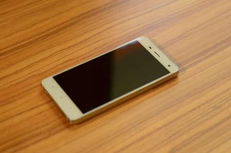 Smartphone met leeg scherm op houten tafel