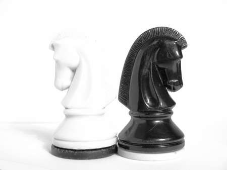 black and white knights standing back to back on light background;