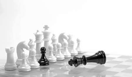 Chess game  White figures in a row with black one and defeated black king  Treason or choice concept  High key  photo