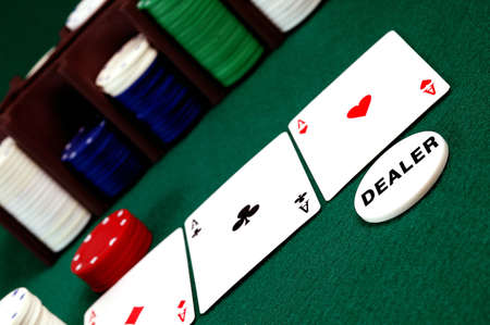 cards and stack of Poker chips and dealer button on a green background photo