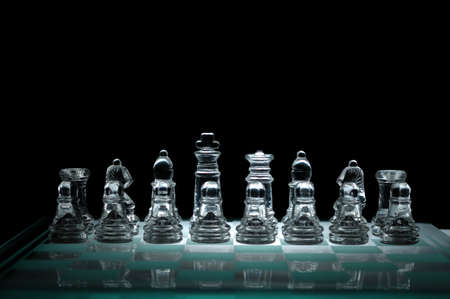 Crystal chess pieces on a row  On black background