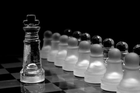 Glass chess pawns in order ,against the king Stock Photo - 12805376