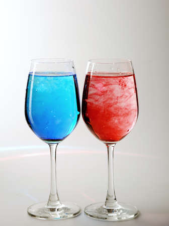 Two wine glasses filled with water and spreading red and blue ink  photo