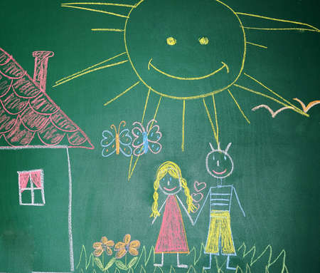 Blackboard with drawing happy couple with house closeup photo