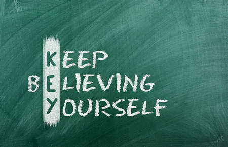 Acronym of KEY  Believe in yourself written in chalk on a blackboard