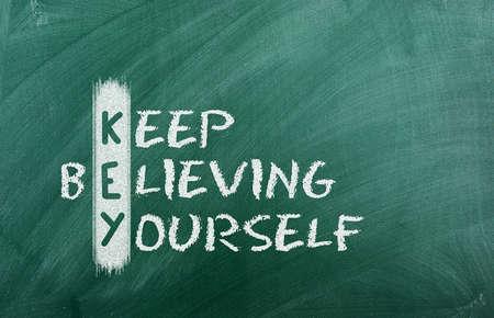 Acronym of KEY  Believe in yourself written in chalk on a blackboard