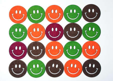 smiling wooden multi colored emoticons in row photo