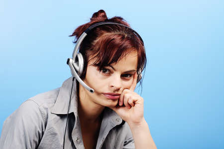 Beautiful young customer assistant wearing a headset with  serious expression  photo