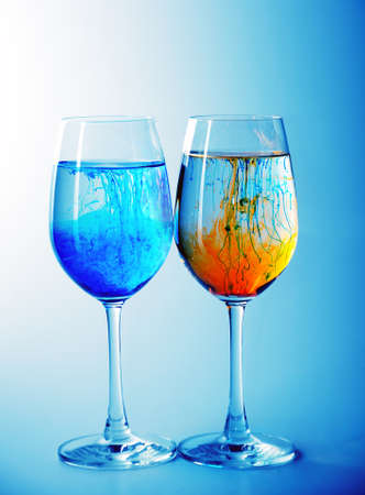 Two wine glasses filled with water and spreading red,yellow  and blue ink  photo