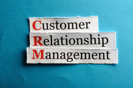 CRM customer relation management abbreviation on blue paper photo