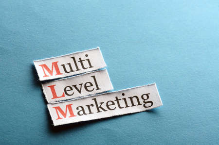 mlm: mlm - multi level marketing on blue paper Stock Photo