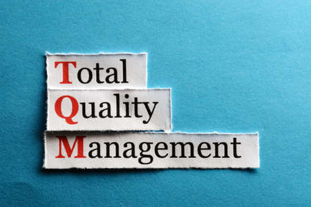 TQM total quality management on blue paper