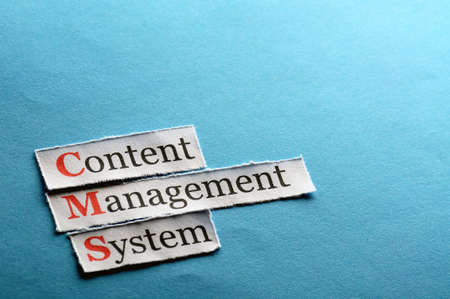 CMS Content Management System abbreviation on blue paper photo
