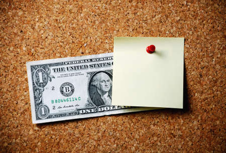 affixed: blank memo note  and dollar bill  affixed to the corkboard Stock Photo
