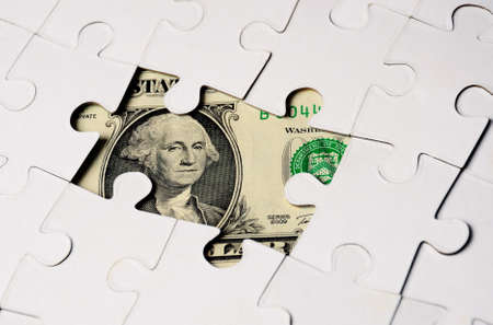 Dollar hidden under  Puzzle, business concept of Solution- close up