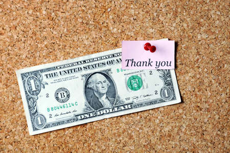affixed: thank you  memo note  and dollar bill  affixed to the corkboard Stock Photo