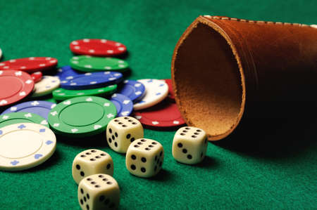 odds: Poker dice with chips on green casino table Stock Photo