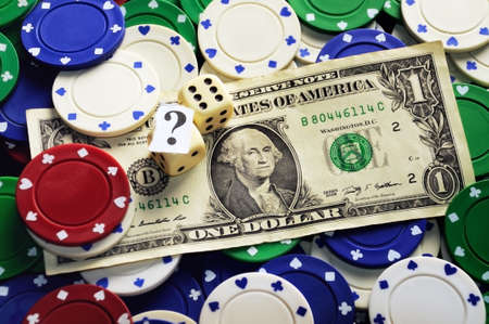 Dollar bill casino chips and dices hidden under  question mark- risk concept photo