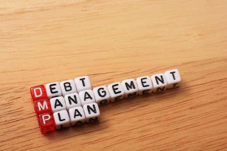 debt management: dices with word DMP debt management plan on wooden  background